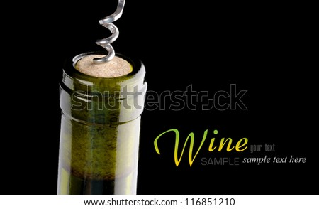 Opening a wine bottle with a cork screw - stock photo