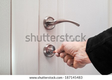 Opening or closing a safety lock on the toilet door
