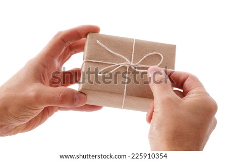 Opening or wrapping a brown recycled paper gift box - stock photo