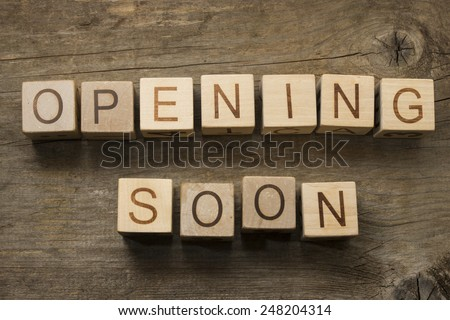 Opening soon text on a wooden cubes on a wooden background - stock photo
