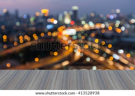 Opening wooden floor, Abstract blurred bokeh lights city and highway intersection with office business area background - stock photo