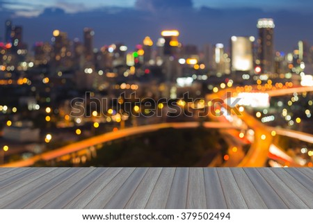 Opening wooden floor, blurred bokeh city downtown lights background at night - stock photo