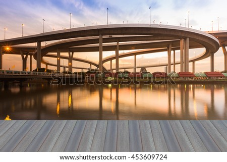Opening wooden floor, Highway interconnection ring with sunset and reflection  - stock photo