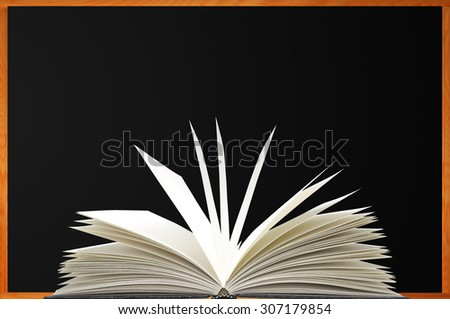 Openned book over blank blackboard with wood frame - stock photo