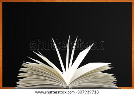 Openned book over blank blackboard with wood frame