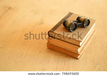 Opera glasses on old books on wooden background
