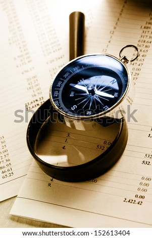 Operating budget, magnifying glass and black compass - stock photo
