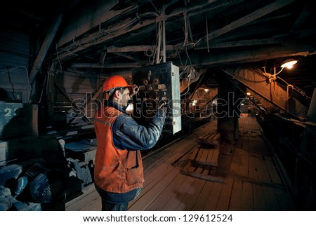 operating mines in the helmet presses a button on the remote control of the conveyor - stock photo