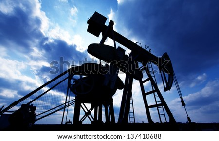 Operating oil and gas well contour, outlined on sky with storm clouds - stock photo