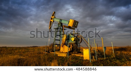 Operating oil and gas well, in remote field, under warm evening light