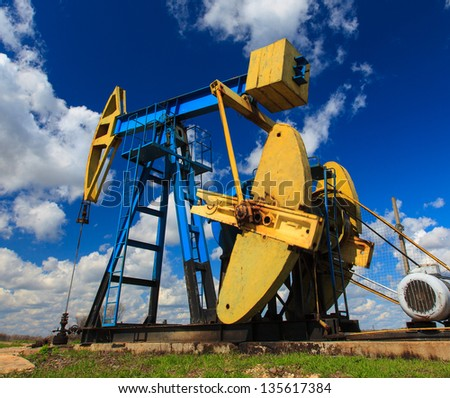 Operating oil and gas well profiled on bright sky with clouds - stock photo