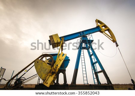 Operating oil and gas well profiled on colorful cloudy sky