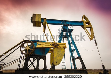 Operating oil well profiled on cloudy sky - stock photo
