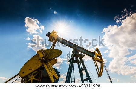 Operating oil well profiled on dramatic cloudy sky
