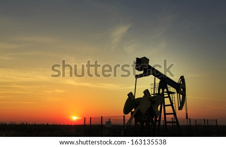 Operating oil well profiled on sunset sky - stock photo
