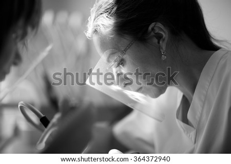 Operating oral surgeon, female doctor's profile in mask  - stock photo