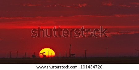 Operational oil wells in sunset colors - stock photo