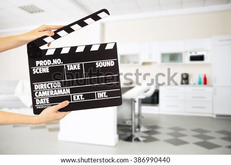 Operator holding clapperboard during the production of film indoors - stock photo