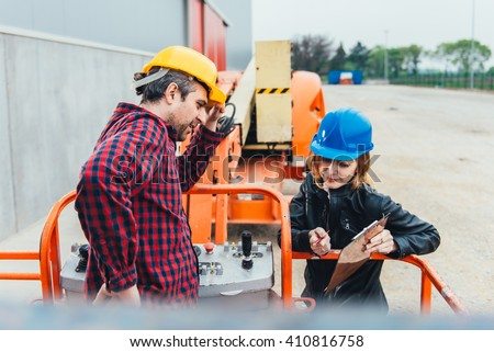 Operator In Safety Helmet and red square shirt receiving instruction for Straight Boom Lift - stock photo