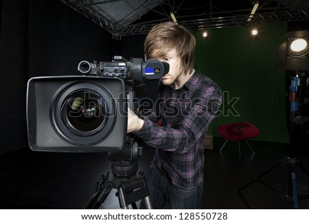 Operator looks into the viewfinder of a television studio camera, with lights and CSO green curtain in the background. - stock photo