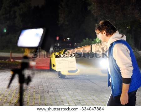 Operator od Director holding clapperboard during the production of movie film outdoor in the night with sportive yellow car in the background.  - stock photo
