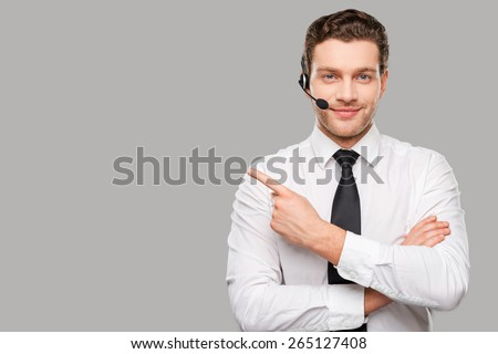 Operator pointing copy space. Handsome young man in formalwear and headset looking at camera and pointing away while standing against grey background - stock photo