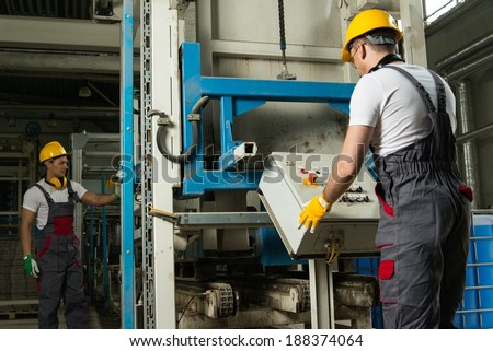 Operator wearing safety hat behind control panel on a factory - stock photo