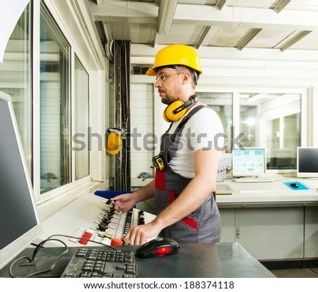 Operator wearing safety hat in a factory control room - stock photo