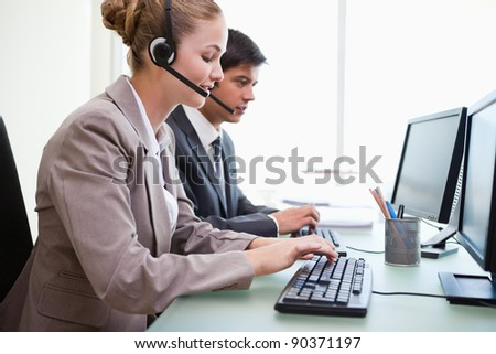 Operators working with computers in an office - stock photo