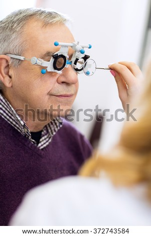 Ophthalmic doctor measure distance of eyes pupil in consulting room - stock photo