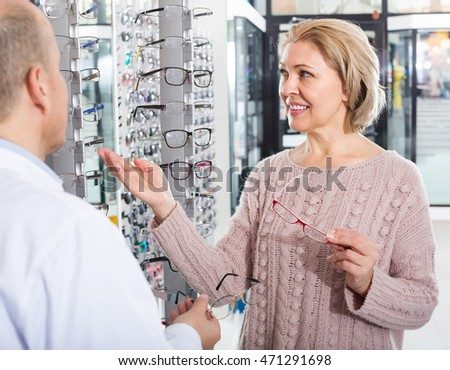 Ophthalmologist and joyful blonde female pensioner choosing glasses in optics store