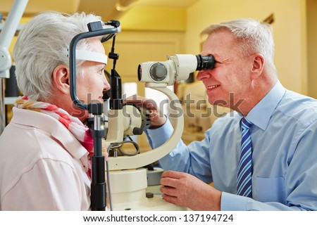 Ophthalmologist examing cornea of senior woman with slit lamp - stock photo