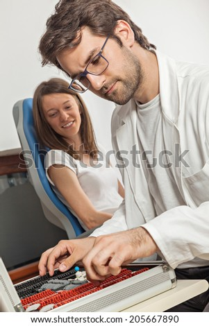 Ophthalmologist With Trial Frame And Patient Behind - stock photo
