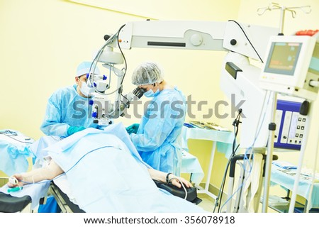 Ophthalmology sergery. surgeon team in uniform in front of eye vision surgery operation room at medical clinic - stock photo
