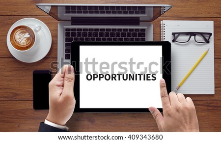 OPPORTUNITIES, on the tablet pc screen held by businessman hands - online, top view - stock photo