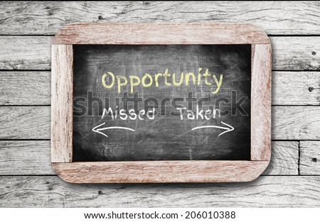Opportunity Missed and Taken written on the blackboard. - stock photo