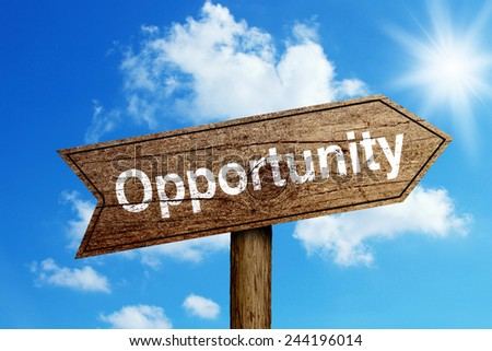Opportunity wooden road sign with shining blue sky background. - stock photo