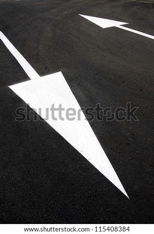 Opposite directions: two up and down white arrows on black asphalt. Challenge contradiction dilemma doubt confusion indecision, pros cons, positive negative, strengths weaknesses, input output, yes no - stock photo