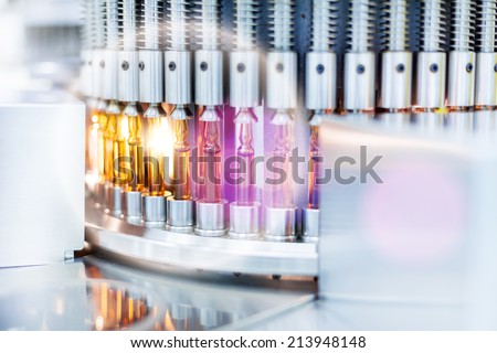 Optical control quality of a vials, pharmaceutical factory.Flare light - stock photo