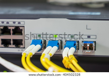 optical fiber cables plug in in network switch - stock photo