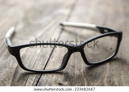 Optical glasses on wooden background, close up