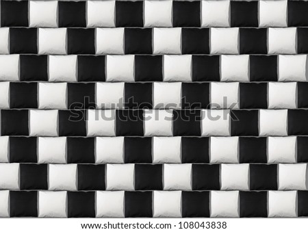 Optical illusion: parallel lines made from black and white pillows - stock photo