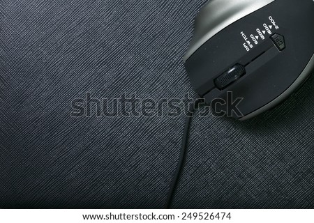 Optical mouse black color with wire put on the black color leather background represent the computer accessory related. - stock photo