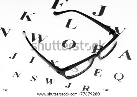 Optical reading glasses on the eyesight table - stock photo