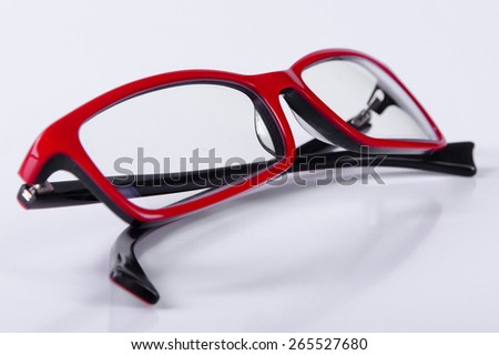 optical red glasses on a light gray background closeup - stock photo