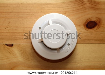 Optical Smoke detector on the wooden background