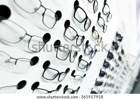 optical store, wall of many fashionable eyeglasses - stock photo