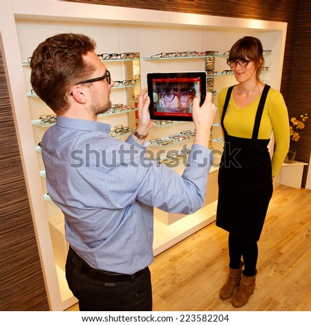 Optician checks glasses with a tablet - stock photo
