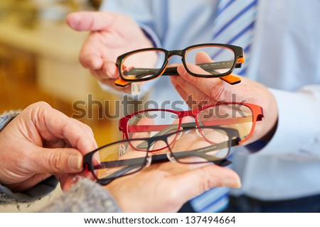 Optician offering a customer a choice of different glasses - stock photo