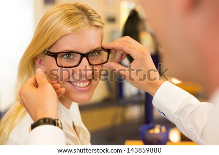 Optician or optometrist consulting a customer about eyeglasses, spectacles and frames in a shop - stock photo